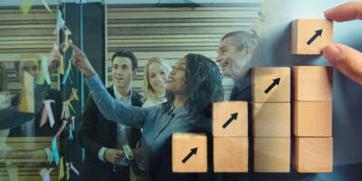 Image of office coworkers smiling together as they work and are all looking at a board with notes. To the right the image fades away to reveal a stack of wooden blocks being stacked on an upward trend.